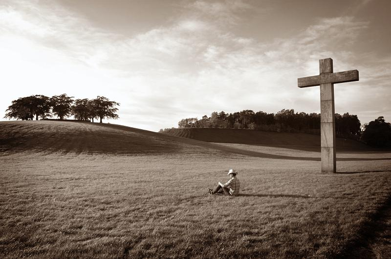Man alone in a field with a cross