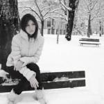 sad woman on park bench in snow