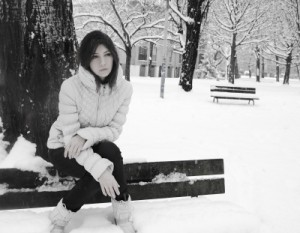 sad woman on park bench in snow